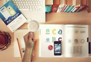 Image représentant plusieurs livres fermés et ouverts, sur un bureau sur lequel il y a également des crayons et un ordinateur ouvert. Quelqu'un tient une tasse dans sa main.